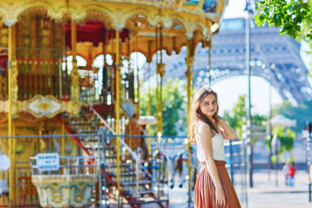 long skirt: Beautiful young Parisian woman in long skirt near the Eiffel tower and traditional French merry-go-round on a summer day