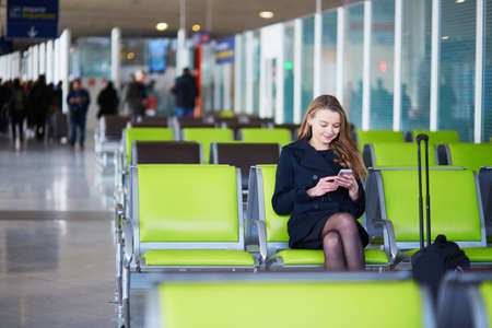 Young woman in international airport, checking her phone while waiting for her flight Stock Photo
