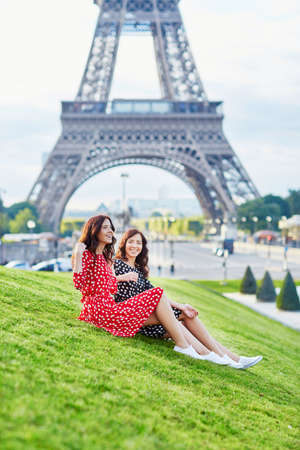 identical: Beautiful twin sisters in red and black polka dot dresses in front of the Eiffel tower in Paris, France