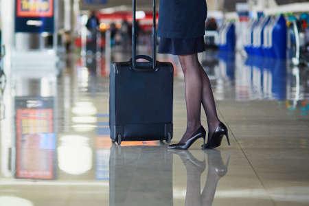 hotesse de l air: Belle passager ou agent de bord féminin dans l'aéroport international avec un bagage à main Banque d'images
