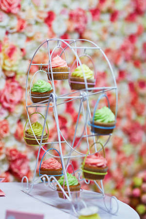 pastel de chocolate: pastelitos de colores en una peque�a rueda de la fortuna, entorno precioso mesa para la fiesta o una boda de recepci�n Foto de archivo