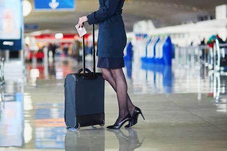 Hermosa asistente de sexo femenino de pasajeros o de vuelo en el aeropuerto internacional con equipaje de mano