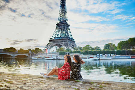 Beautiful twin sisters in red and black polka dot dresses in front of the Eiffel tower near the river Seine in Paris, France