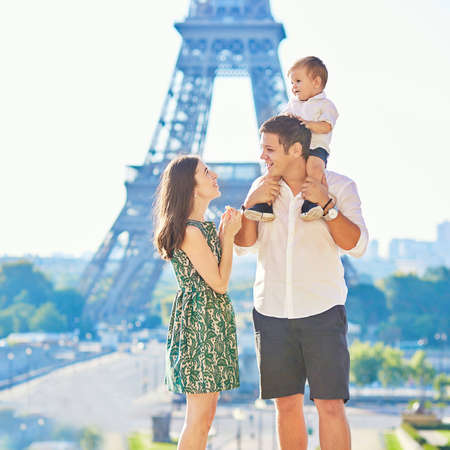 husband and wife: Happy family of three standing in front of the Eiffel tower and enjoying their vacation in Paris, France