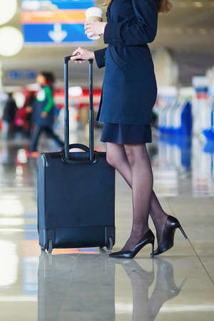 airline hostess: Beautiful female passenger or flight attendant in international airport with hand luggage