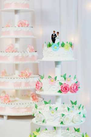 lovely women: White wedding cake decorated with pink sugar flowers and bride and groom figurines on top Stock Photo