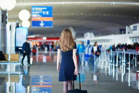 air hostess: Jeune femme à l'aéroport international, à pied avec ses bagages, vue de dos. hôtesse de l'air allant à la rencontre de son équipage Banque d'images