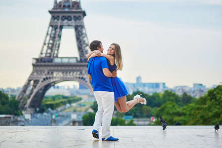 hugged: Romantic dating couple on Trocadero viewpoint in Paris, man is rotating his hugged girlfriend around, Eiffel tower is in the background Stock Photo