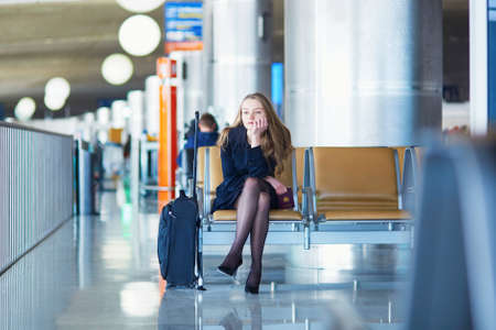 business traveller: Young woman in international airport, waiting for her flight and looking upset or worried. Missed, canceled or delayed flight concept Stock Photo
