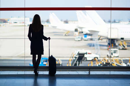 Young woman in the airport, looking through the window at planes