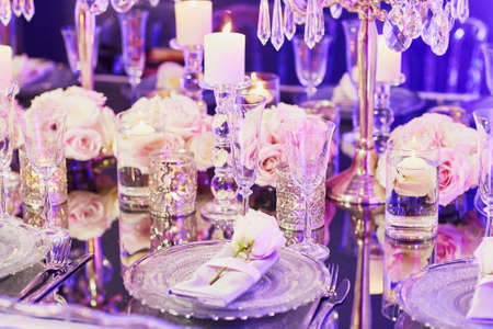 candleholder: Beautiful table set with candles and flowers for a festive event, party or wedding reception, in purple light