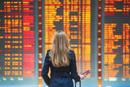 Mujer joven en el aeropuerto internacional de mirar la tabla de información de vuelo, que controla su vuelo Foto de archivo