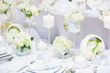 Belle table dressée avec des bougies et des fleurs pour une réception festive événement, fête ou de mariage