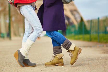lesbianas: Detalle de las piernas femeninas, dos muchachas que abrazan en la calle en París, el concepto de relación del mismo sexo