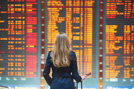 schedule: Young woman in international airport looking at the flight information board, holding passport in her hand, checking her flight Stock Photo
