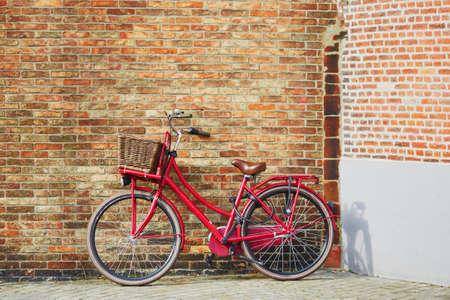Red bicycle against brick wall in Brugge, Belgium