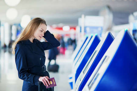 flight: Young woman in international airport doing self check-in, stressed and concerned. Missed, delayed or canceled flight concept Stock Photo