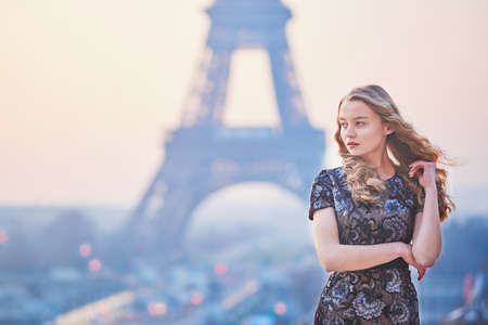 paris france: Beautiful elegant Parisian woman near the Eiffel tower at early morning