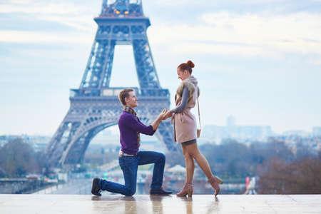 Romantische engagement in Parijs, de mens stelt voor om zijn mooie vriendin in de buurt van de Eiffeltoren