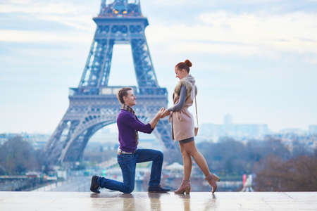 Romantic engagement in Paris, man proposing to his beautiful girlfriend near the Eiffel tower Standard-Bild