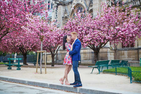 romantic man: Young couple in love having a date under pink cherry blossom trees, Notre-Dame cathedral in the background.