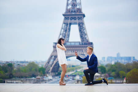 suddenness: Romantic engagement in Paris, man proposing to his beautiful girlfriend near the Eiffel tower. Stock Photo