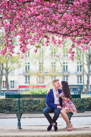sweethearts: Romantic couple having a date in Paris on a spring day with beautiful cherry blossoms in the background Stock Photo