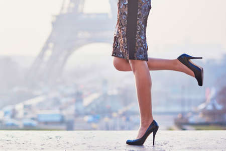 Woman wearing high heels shoes and walking near the Eiffel tower at early morning in Paris, closeup of legs Stock Photo - 57105039