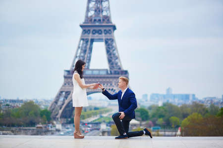 exaltation: Romantic engagement in Paris, man proposing to his beautiful girlfriend near the Eiffel tower. Stock Photo