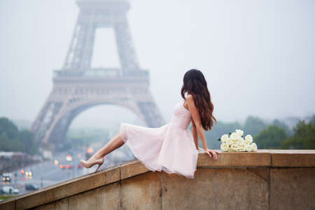 Elegant Parisian woman with white roses looking at the Eiffel tower from Trocadero view point Standard-Bild