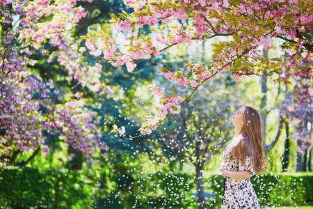 Mooie jonge vrouw genieten van zonnige dag in het park tijdens de kersenbloesem seizoen op een mooie lentedag