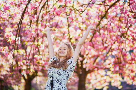 flowering: Beautiful young woman enjoying sunny day in park during cherry blossom season on a nice spring day