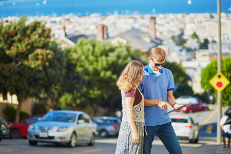 frisco: Romantic couple of tourists using tablet and planning their itinerary in San Francisco, California, USA Stock Photo