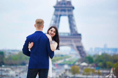 romantic date: Happy couple near the Eiffel tower. Tourists enjoying their vacation in France. Romantic date or traveling couple concept