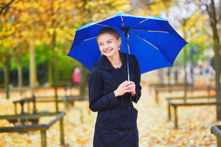 april: Beautiful young woman with blue umbrella in the Luxembourg garden of Paris on a fall or spring rainy day