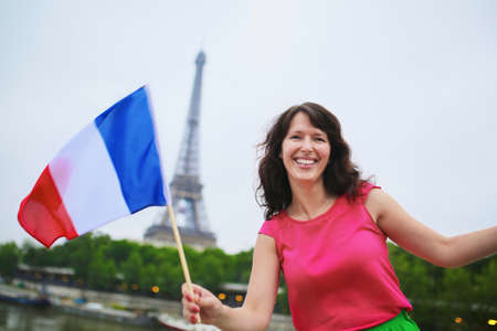 national holiday: Cheerful young woman with French national flag, tricolor, having fun near the Eiffel tower in Paris, France. 14th July national holiday concept