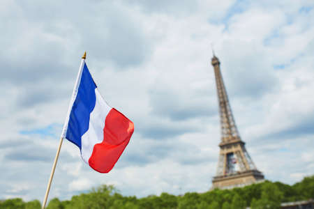 14th: French national flag (tricolour) in Paris with the Eiffel tower in the background. July the 14th, French national holiday concept