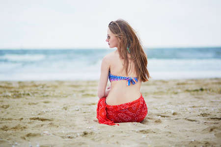 pareo: Beautiful young woman in bikini and red pareo sitting on the sand on beach, relaxing and sunbathing. Summer vacations concept