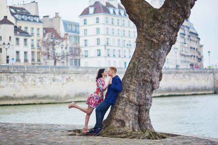 romantic date: Happy couple kissing on the bank of the Seine in Paris. Tourists enjoying their vacation in France. Romantic date or traveling couple concept