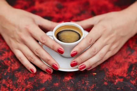 french manicure sexy woman: Beautiful woman hands with red manicure and cup of fresh hot coffee on wooden table