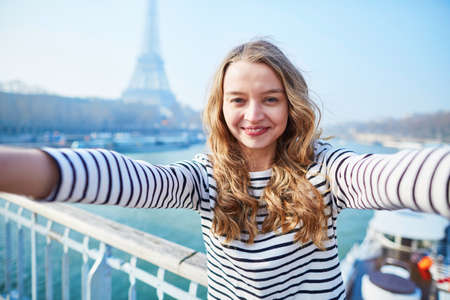 touristic: Beautiful young girl taking funny selfie with her mobile phone near the Eiffel tower