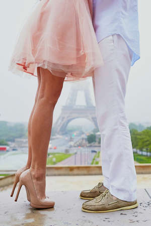 Closeup of male and female legs during a date, Eiffel tower in the background. Romantic couple in Paris, kissing or hugging near the Eiffel tower 版權商用圖片