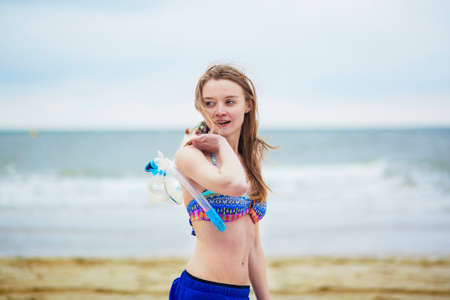 snorkelling: Happy young woman with snorkelling equipment in bikini enjoying summer vacation holidays by ocean or sea. Beach, travelling and people concept Stock Photo