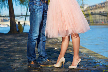 romantic date: Closeup of male and female legs during a date. Romantic couple kissing on the Seine embankment in Paris