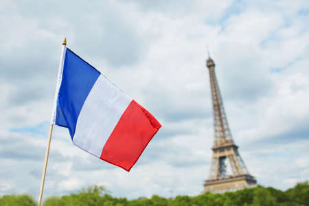 tricolour: French national flag (tricolour) in Paris with the Eiffel tower in the background. July the 14th, French national holiday concept