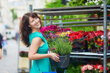 french woman: Cheerful happy young French woman selecting flowers on market, holding a flower pot with lavender. Paris, France