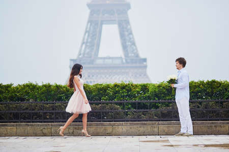 Beautiful romantic couple in love having a date near the Eiffel tower in Paris on a cloudy and foggy rainy day, man is offering huge bunch of white roses to his girlfriend