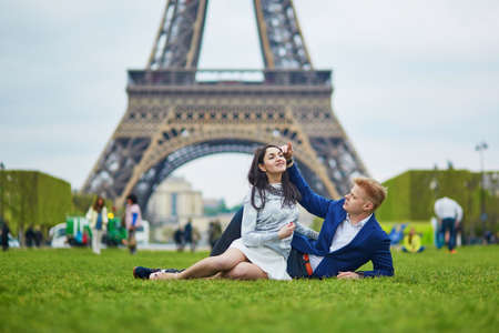 Happy couple lying on the grass near the Eiffel tower. Tourists enjoying their vacation in France. Romantic date or traveling couple concept Stock Photo