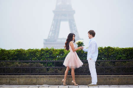 romantic date: Beautiful romantic couple in love having a date near the Eiffel tower in Paris on a cloudy and foggy rainy day, man is offering huge bunch of white roses to his girlfriend