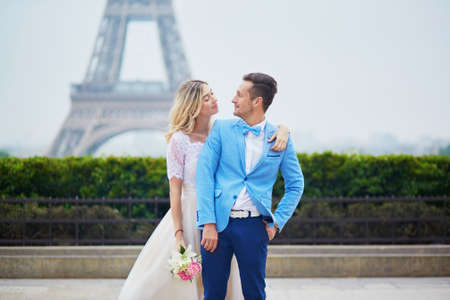 fiancee: Just married couple near the Eiffel tower on their wedding day. Bride and groom in Paris, France Stock Photo